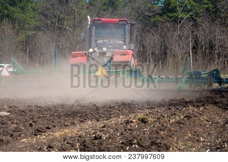 Farmer On A Powerful Tractor Cultivates The Field In The Spring Before Planting Wheat