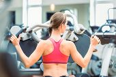 Side view of a determined and beautiful fit woman cycling on stationary bicycle during workout for burning calories at the gym poster