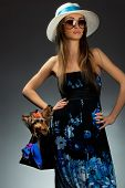 Young glamor woman with Yorkshire Terrier dog in her bag poster