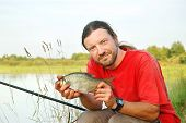 Fisherman holding a bream on the shoreline of a river poster