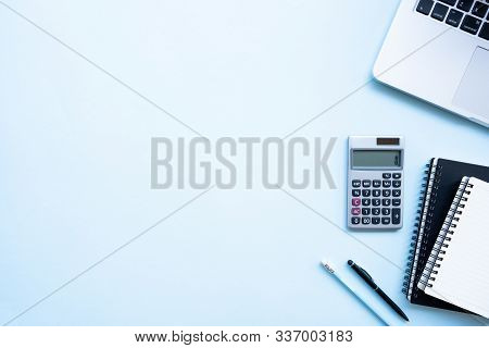 Flat Lay, Top View Office Table Desk. Workspace With Calculator, Black Pen , Laptop On The Indigo Bl