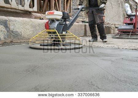 The Workers Grind The Concrete Floor At The Construction Site