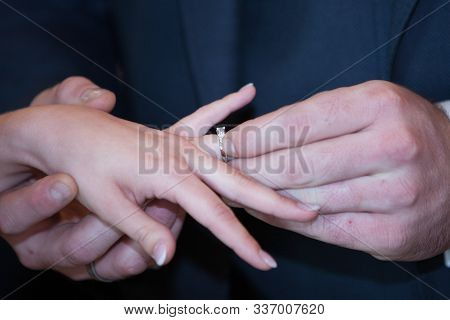 An Unrecognizable Bride And Groom Exchanging Of The Wedding Rings In Church During The Christian Wed