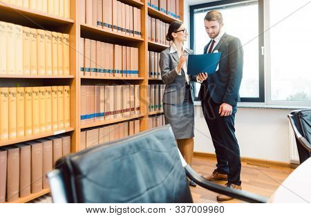 Two lawyers in library of law firm discussing strategy in a case holding file