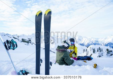 Photo of skis, ski poles against background of two sports women with thermos sitting in ski resort in winter.