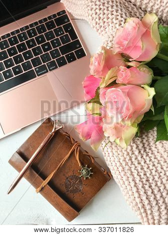 Womens Workspace With Laptop, Bouquet Of Pink Roses, A Notebook, A Pen And A Cosy Blanket In A Flat