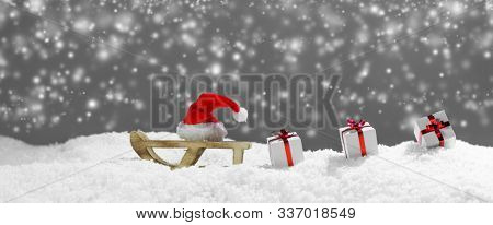 Christmas card decoration: santa claus hat on sleigh and presents on snow