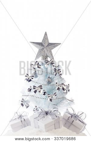 White christmas tree with silver decorations and gifts on snow isolated on white background
