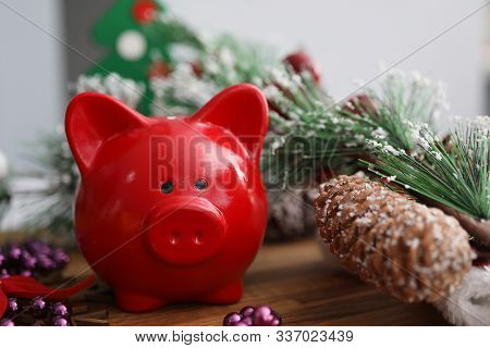 Close-up Of Bright Red Piggy-bank On Wooden Table. Pinecones And Nice Purple Beads Decorations. Spri