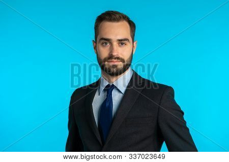 Close Up Portrait Of Young Successful Confident Businessman With Beard Isolated On Blue Studio Backg