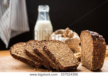 Loaf Of Rye Bread With Seeds Sliced On Wooden Cutting Board. Copy Space For Text. Healthy Sourdough