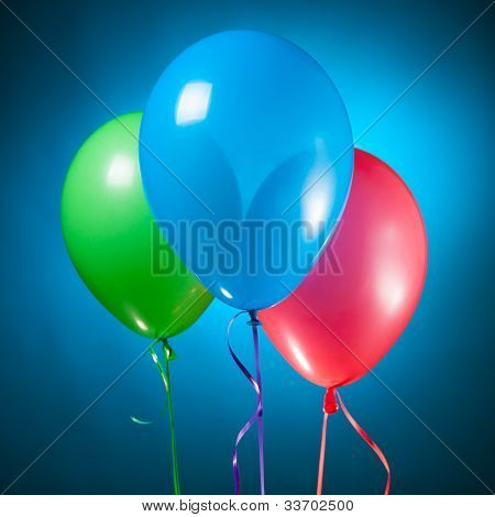 group of festive multicolor rgb balloons on blue poster