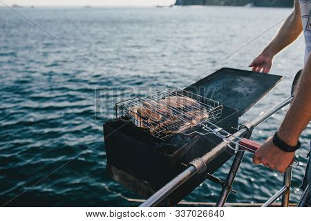 Man Grilling Fish On Yacht With Beautiful Ocean View.