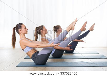 Group Of Young Sporty Attractive Women In Yoga Studio, Practicing Yoga Lesson With Instructor, Formi