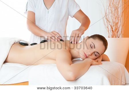 Positioning warm stones on back for lastone therapy at spa center