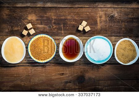 Different Kinds Of Sugar And Sweeteners In The Bowls, Such As Coconut, Pure Cane, Icing, Maple Syrup