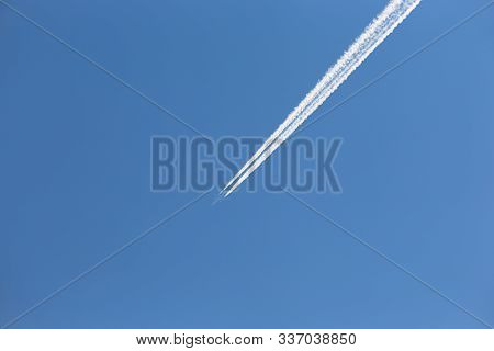 Almost Invisible Passenger Airplane With Inversion Trace Over Clear Sky Background