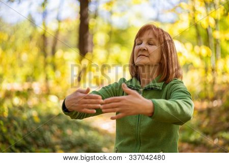 Senior Woman Is Practicing Tai Chi Exercise In Park.