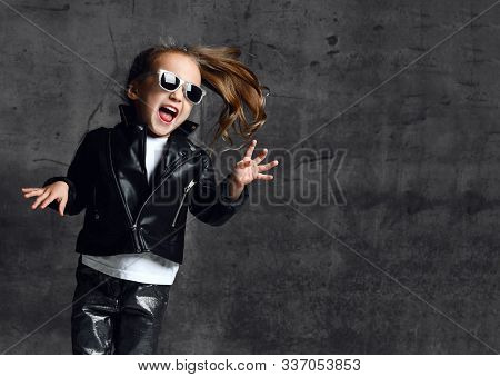 Cheerful Screaming Kid Girl Frolic In Leather Jacket, Jeans And Sunglasses Is Playing Having Fun Sin