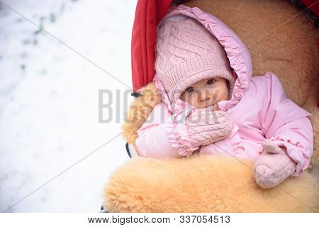 Cute Baby In Stroller On Frosty Winter Day. Baby Wearing Woolen Warm Hat And Mittens And Lying In La