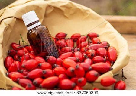Rose-hips And Rose Hip Seed Oil On The Wooden Table. Rose Hip  Commonly Known As Rose Hip (rosa Cani