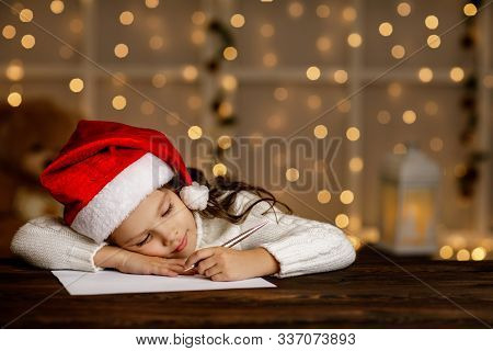 Happy Little Child Girl In Santa Hat Writing Wish List Or Letter To Santa Claus On Background With L