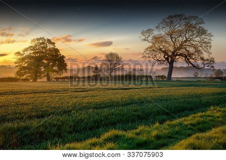 Sunrise Rural Landscape With Mist And Pink Skies In Norfolk Uk. Spring Time Scene With Fields, Crops