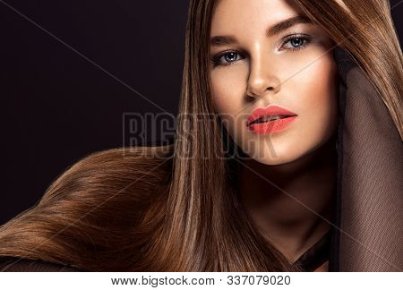 Woman with beauty long brown hair. Beautiful  model with long straight hair. Model with a smokey makeup. Pretty woman with orange color lipstick on lips. Pantone 2019.