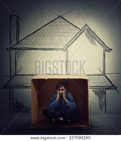 Stressed Teenage Boy Sitting Inside A Cardboard Box Hut, Imagine A Big House. Improvised Shelter Of