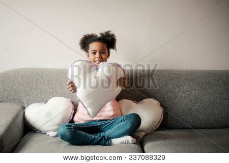 Little Black girl holding a heart shape pillow and sitting on a couch.