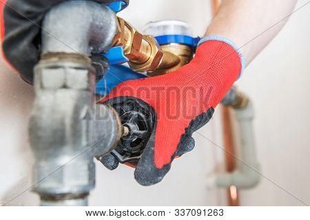 Residential Water Pipeline Valve Closing. Plumbing Industry Concept. Caucasian Plumber Worker.