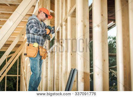 Wood House Frame Construction And The Contractor Worker In His 30s With Drill Driver Attaching Woode