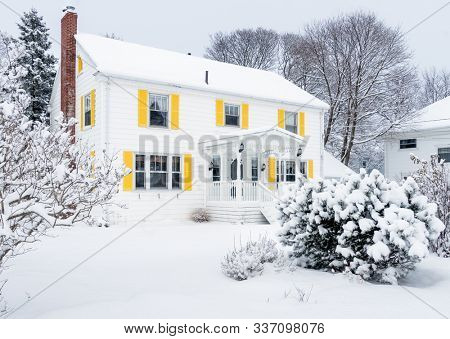 Tradional older family home covered in snow.