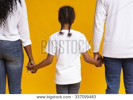 Adoption Concept. Little Afro Girl Holding Hands Of Her Adoptive Parents, Walking Together Over Yell