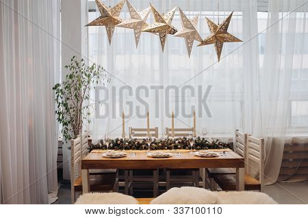 Beautiful Christmas Serving Table With Candles And Fir-tree Decoration At Cozy Modern Interior