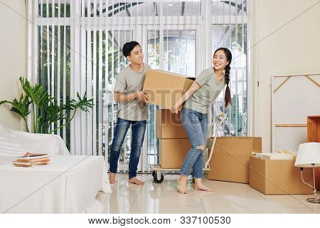 Happy Young Vietnamese Couple In Casual Clothes Carrying Heavy Cardboard Box When Moving In New Hous
