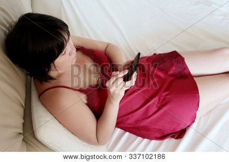 Woman With Smartphone In Bed, Home Leisure. Sexy Girl Wearing Red Nightie Laying In Bedroom With Pho