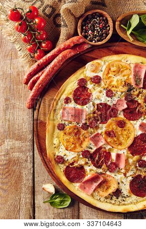 Meat and tomato pizza on wooden table top view. Ham slices, hunter sausages and caramelised onion ingredients on dough composition. Italian takeout dish. Baked snack with salami and cheese