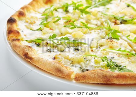 White four cheeses pizza with blue mold cheese, goat cheese, mozzarella and parmesan top view isolated. Traditional italian whole flatbread or ai quattro formaggi with fresh arugula