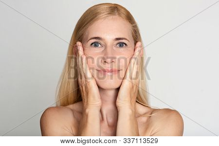 Anti Aging Treatment. Middle-aged Woman Touching Cheeks Over Grey Studio Background