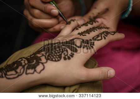 The Process Of Drawing A Henna Mehendi Drawing On The Girl Hand. Tattoo Painting Henna