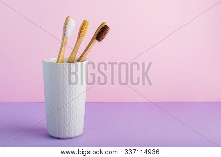 Natural Bamboo Toothbrushes In Glass On Color Pink Background. Biodegradable Natural Bamboo Toothbru