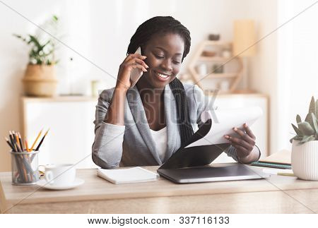 Business Consulting. Black Female Manager Making Phone Call And Checking Reports In Modern Office.