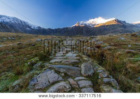 Early Morning Light And Shadow Over Mountains And Snow. Y Garn And  Glyder Farw. Stone Path In Centr
