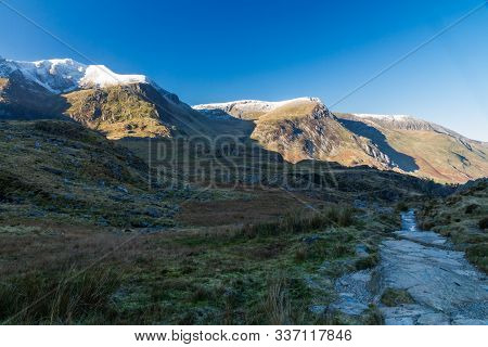 Early Morning Light And Shadow Over Mountains And Snow. Snow Capped Mountains, Y Garn And Foel Goch,