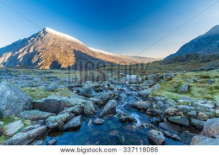 Early Morning Light And Shadow Over Mountains And Snow. Stream  In Foreground And Mountain  Carnedd