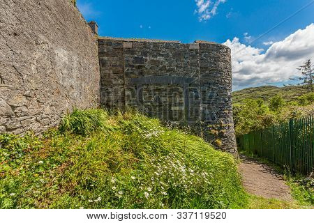 Stone Walls Of The Old Bridewell Gaol Next To A Small Path And A Metal Fence With Mountains In The B