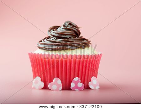 Vanilla Cupcake With Chocolate Icing In Nice Paper Mold, Earths And Pink Background