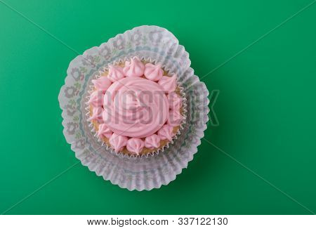 Delicious Sweet Vanilla Cupcake With Pink Icing Sugar, Green Background