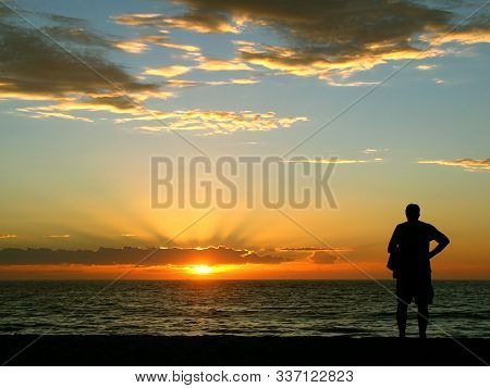 In Images An Elderly Man Watches A Beautiful Sunset At The Sea. The Man Sits Motionless With His Bac